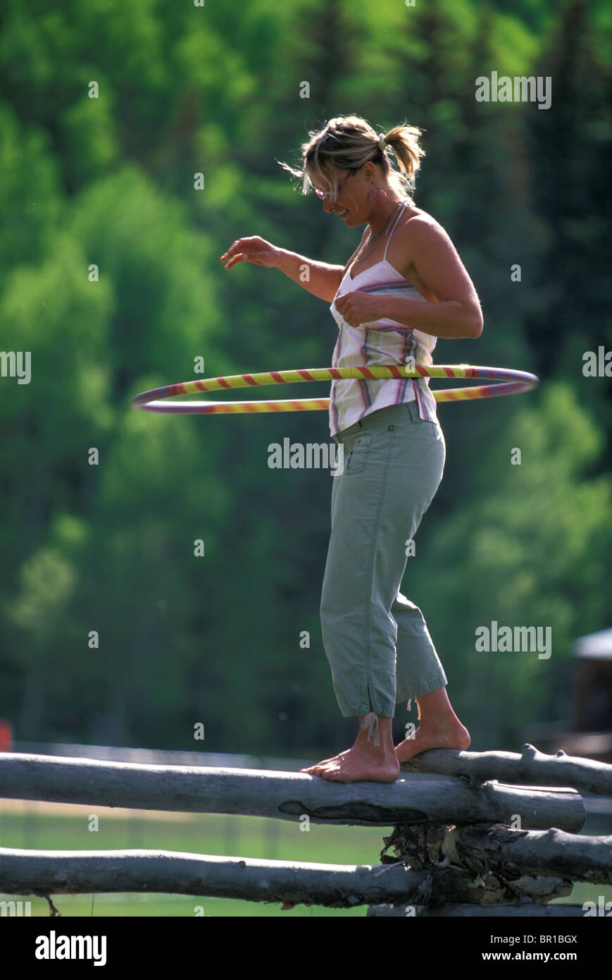 A woman hula hooping while balancing on a fence in Telluride, Colorado (Back Lit). - Stock Image