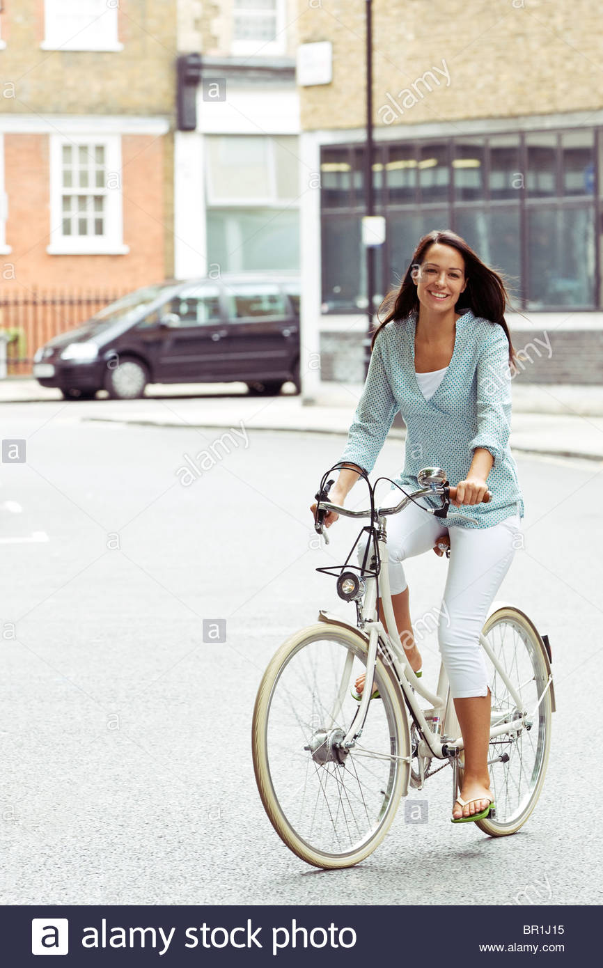 A young woman riding her bicycle in the street - Stock Image