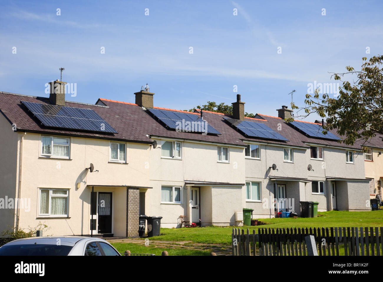 Row of urban terraced houses with solar panels on the roof in a residential council estate street. Llangefni Isle - Stock Image