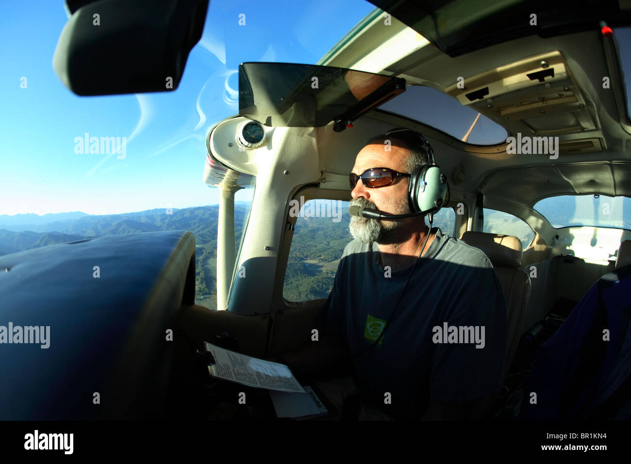 Male pilot at the controls of a Cessna 182 above the Appalachian Mountains near Asheville, NC - Stock Image