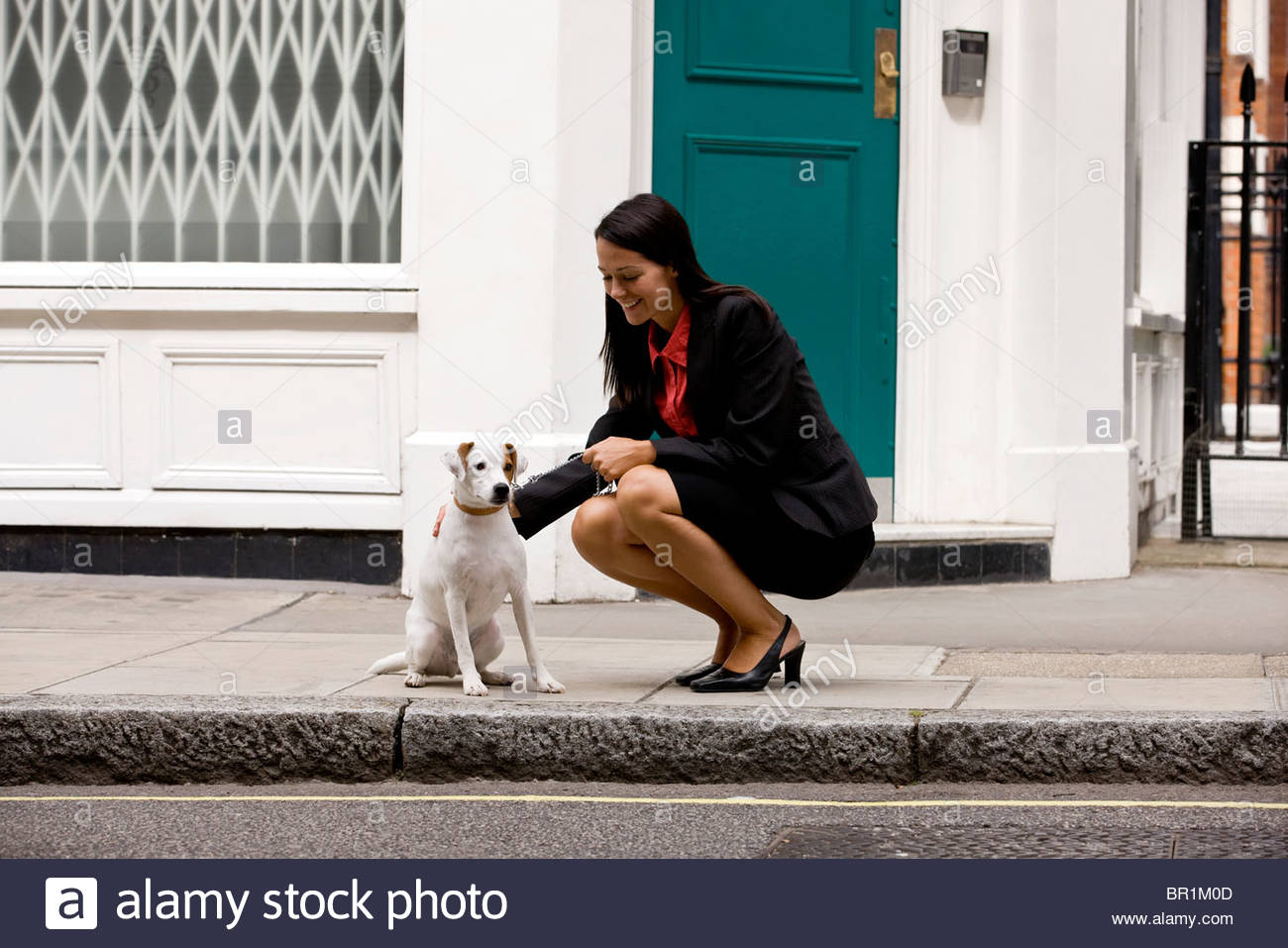 A businesswoman stroking her dog in the street - Stock Image