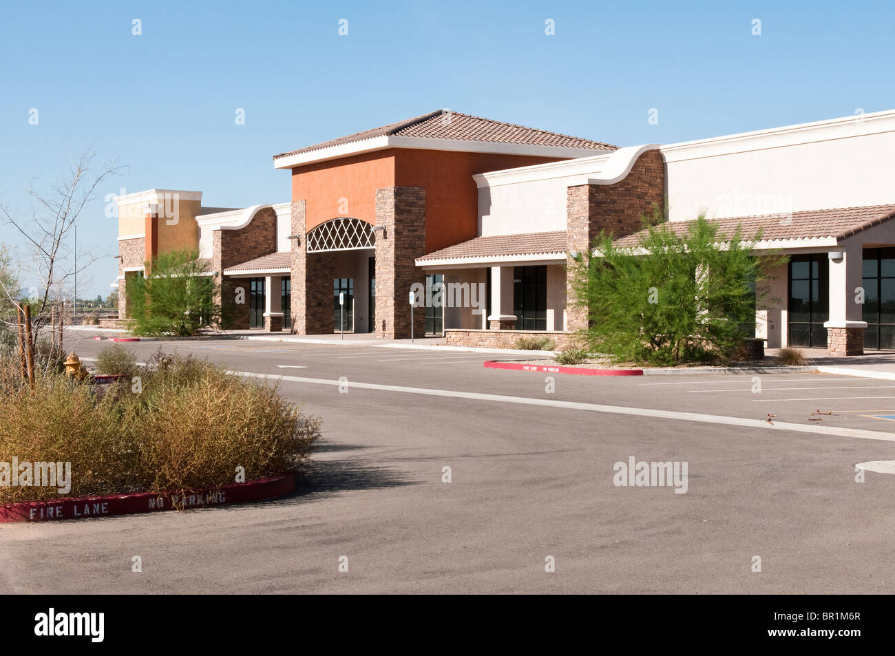Retail spaces stand empty in an abandoned development project. - Stock Image