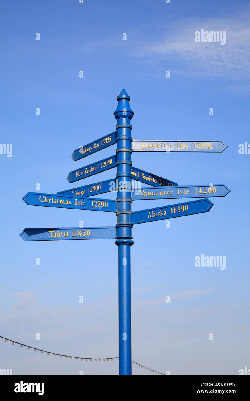 Signpost showing destinations and distances of Captain James Cook's voyages from Whitby, North Yorkshire, England, - Stock Image