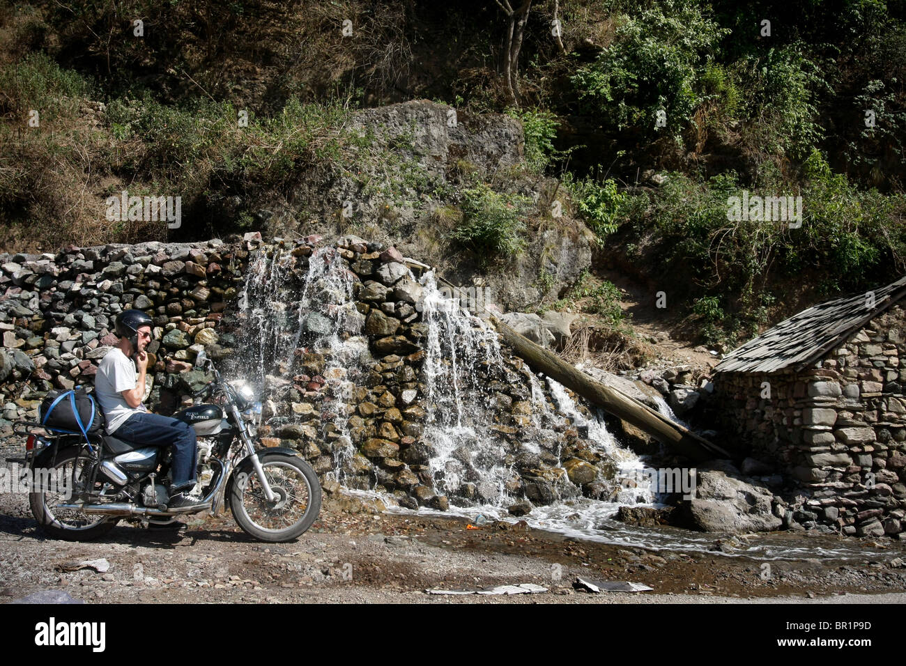 A man sits on a Royal Enfield 'bullet' motorbike during a motorcycle tour in the Himalayas in  Himachal - Stock Image