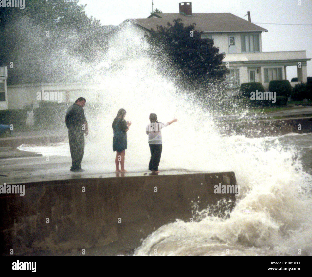 A local family stand on the seawall at Woodmont Point during high tide in Milford Conn. Hurricane Floyd was reduced - Stock Image