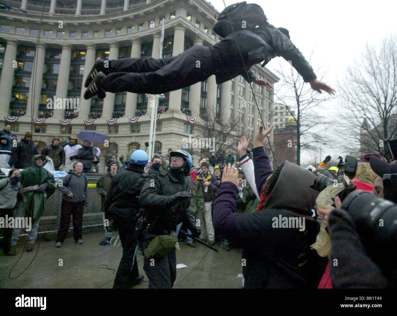 A protester jumps from the navy Memorial over the head of a policeman at president George W. Bush's inauguration - Stock Image