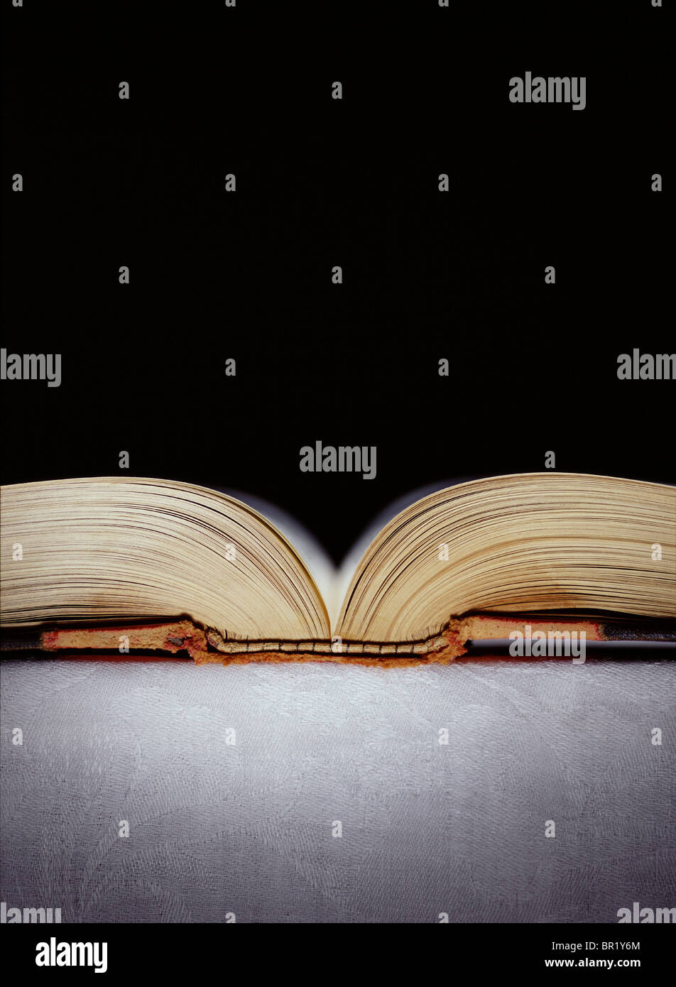 Book laying open on a table surface with black background. - Stock Image