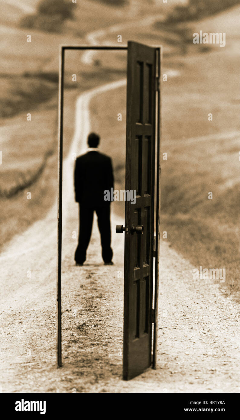 conceptual photograph of executive man standing on country road framed with an 'open door' - Stock Image