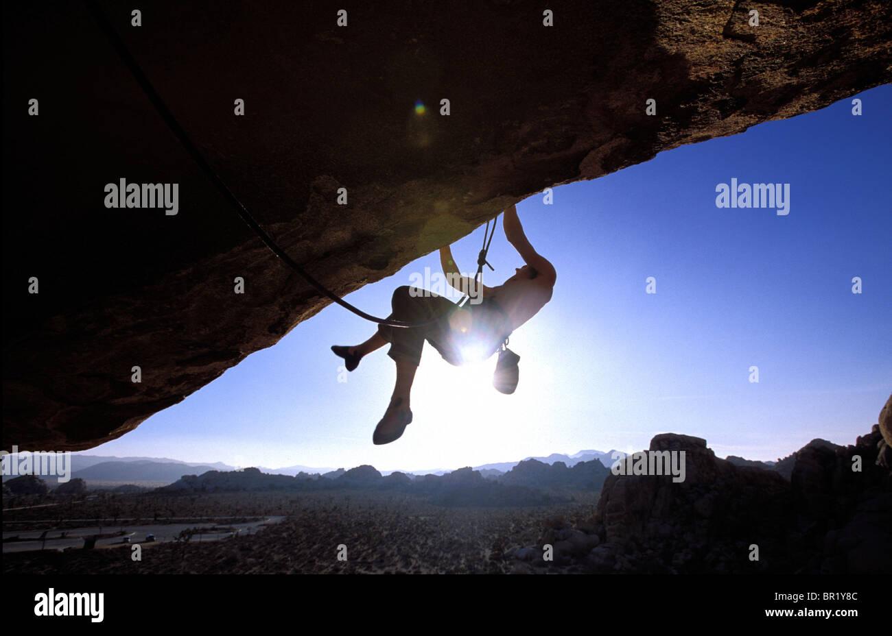 Man climbing on an overhang in Joshua Tree NP, California (Silhouette). - Stock Image