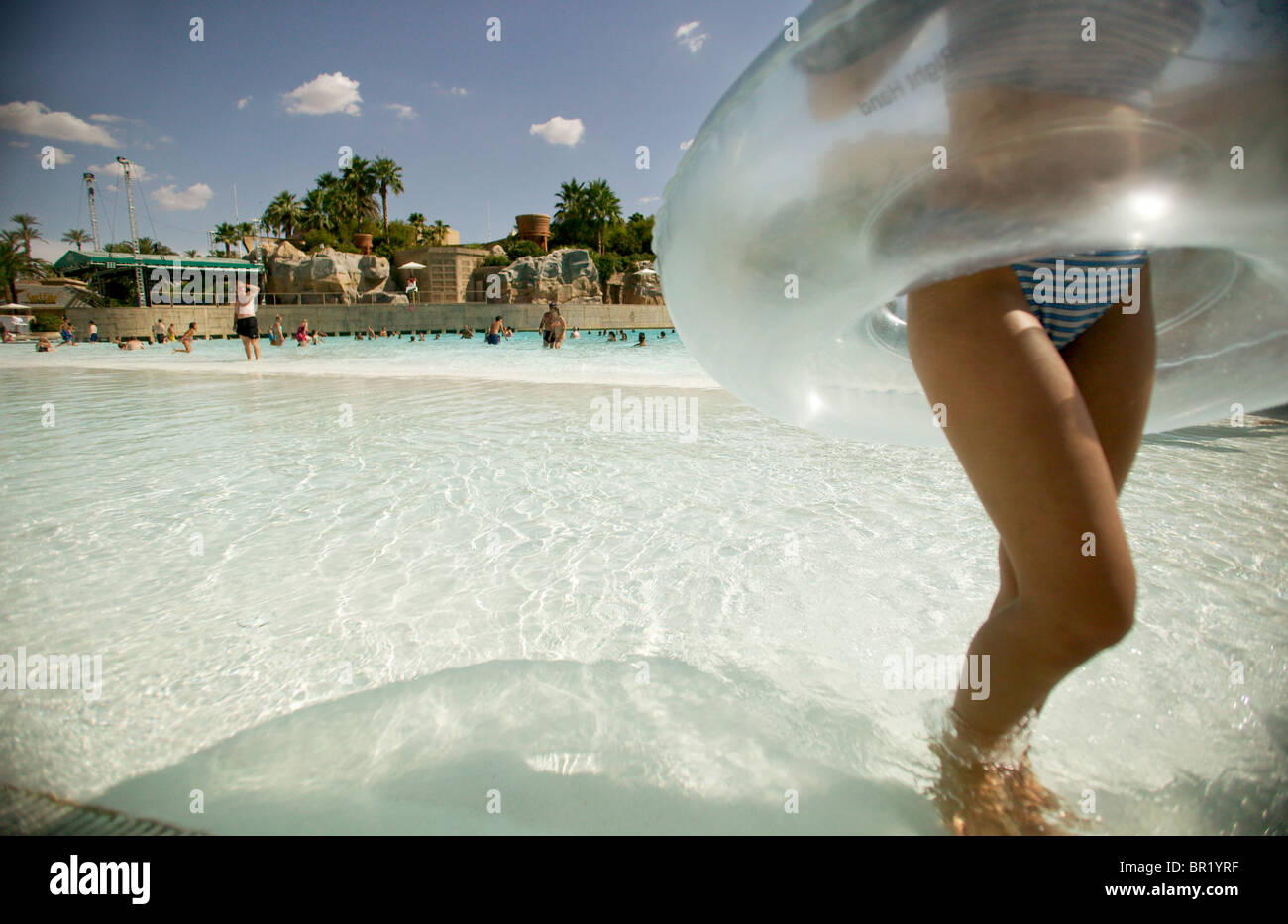 Girl running in pool with an inner tube around her waist. - Stock Image
