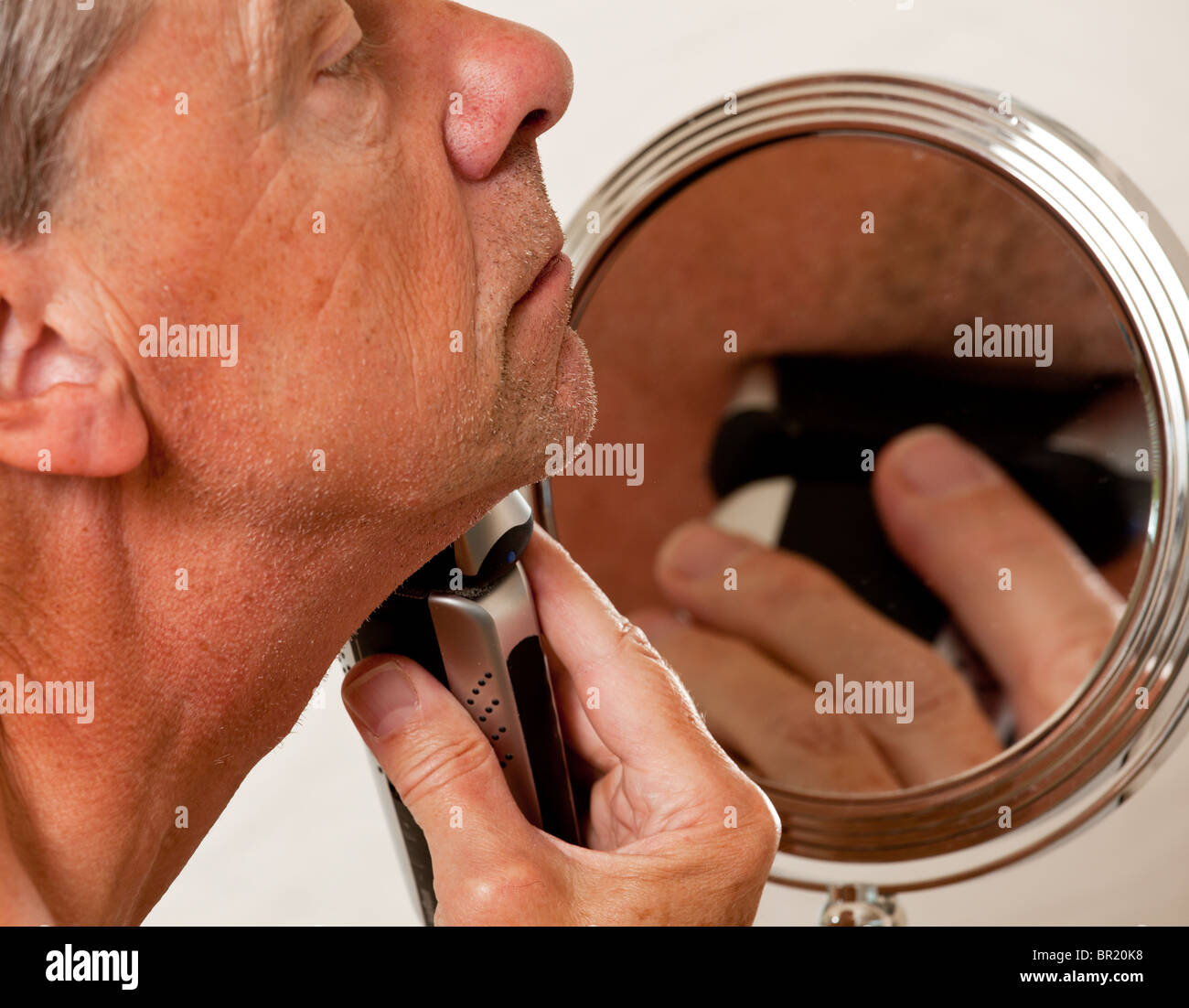 Retired senior man shaving with electric razor in front of magnifying mirror - Stock Image