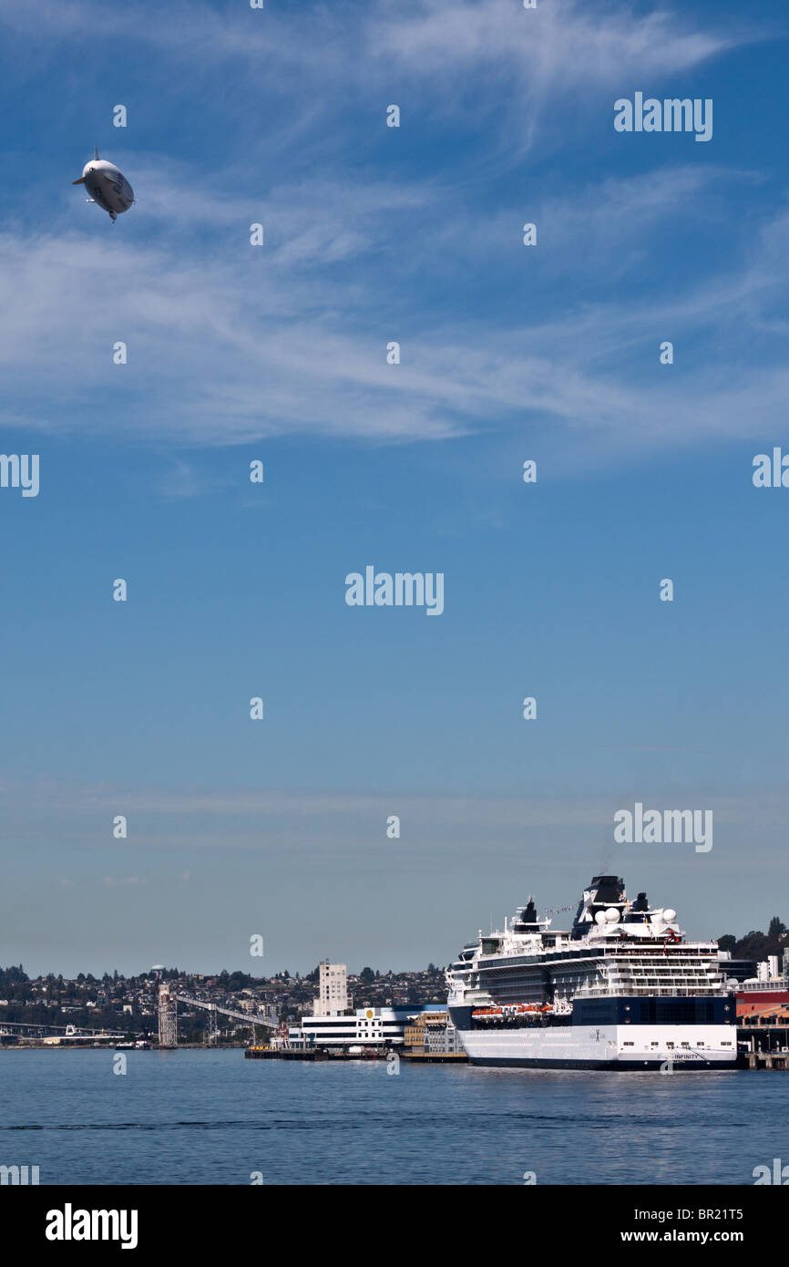 Blimp flies above Celebrity Cruise Lines cruise ship at pier 66 on the Seattle, Washington waterfront - Stock Image