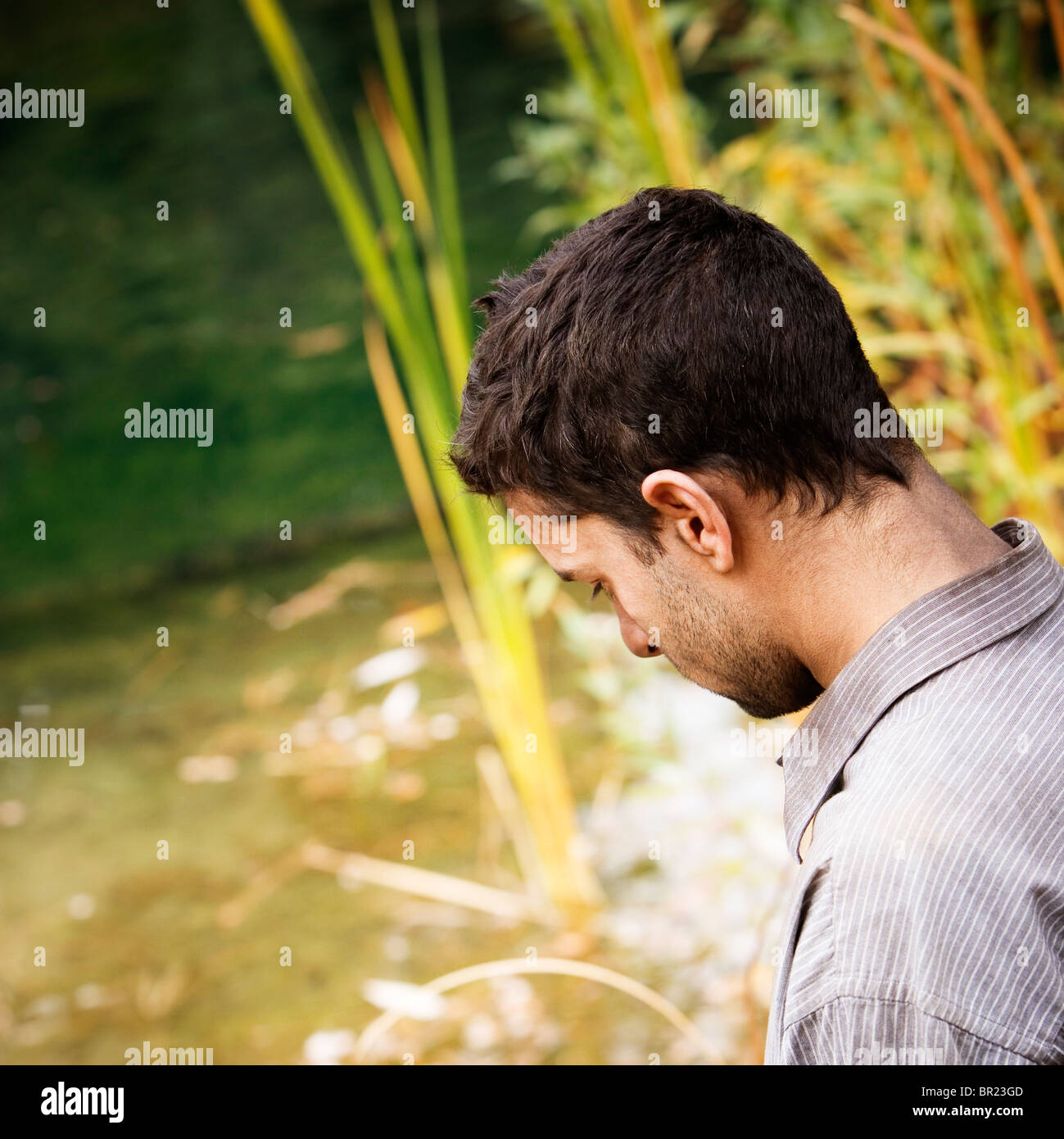 Side view of a man looking down. - Stock Image