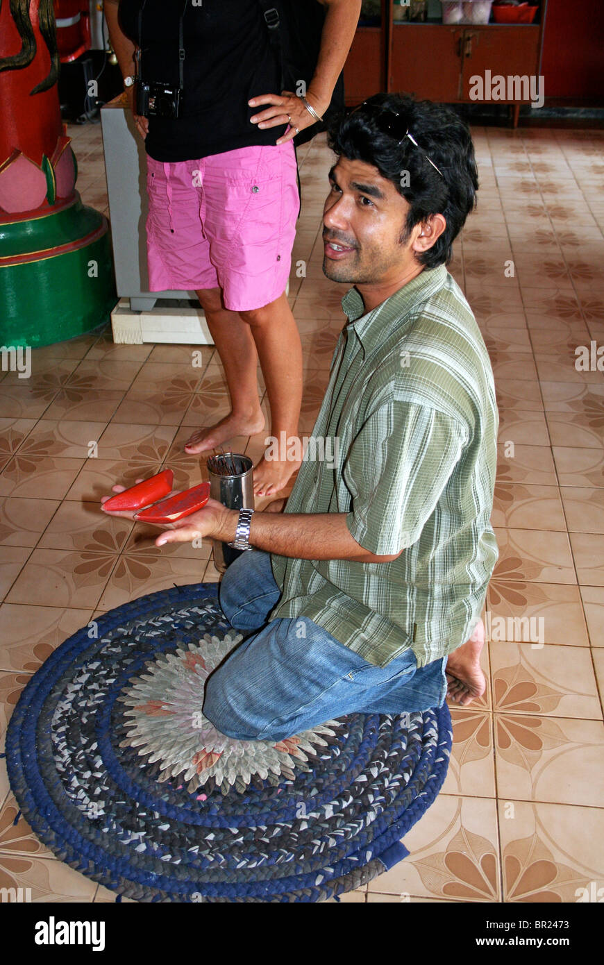 Tour Guide demonstrates fortune telling in a Chinese Taoist Temple, Phuket Island, Thailand, Far East. - Stock Image