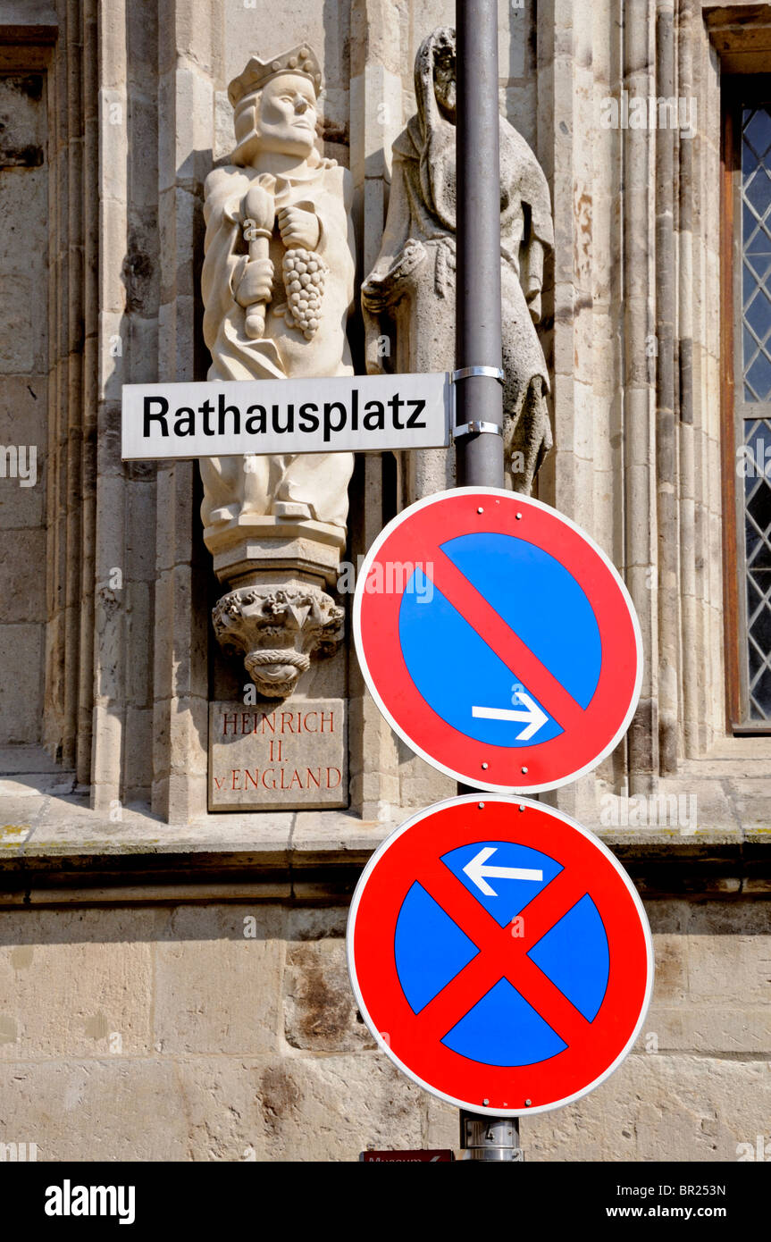 Cologne / Koln, Nordrhein-Westfalen, Germany. Road signs in Rathausplatz. Statue on town hall of Henry II of England - Stock Image