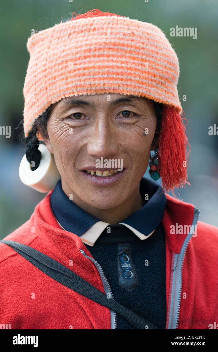 Mixing western sports wear with traditional Tibetan jewelry, Tibetan buys supplies, Xin Du Qiao, Sichuan Province, - Stock Image