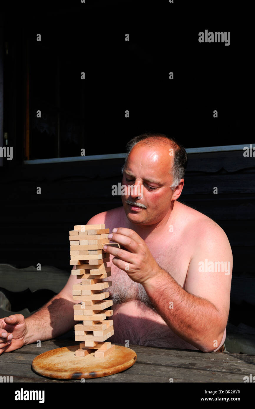 Mature Man playing a tricky board game - Stock Image