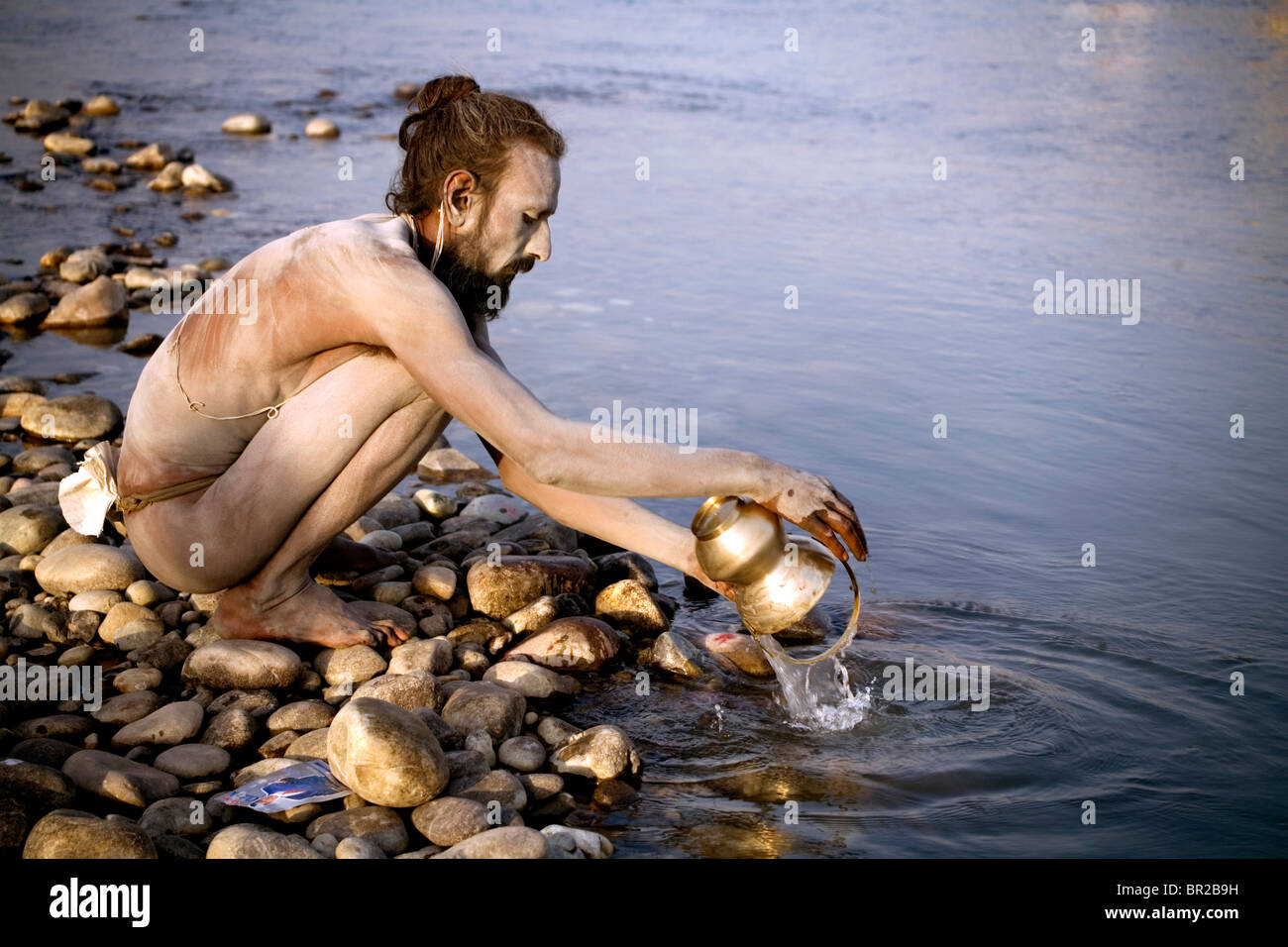 A Sadhu holy man is washing his bowl in river Ganges, Haridwar, Uttarakhand, India. - Stock Image