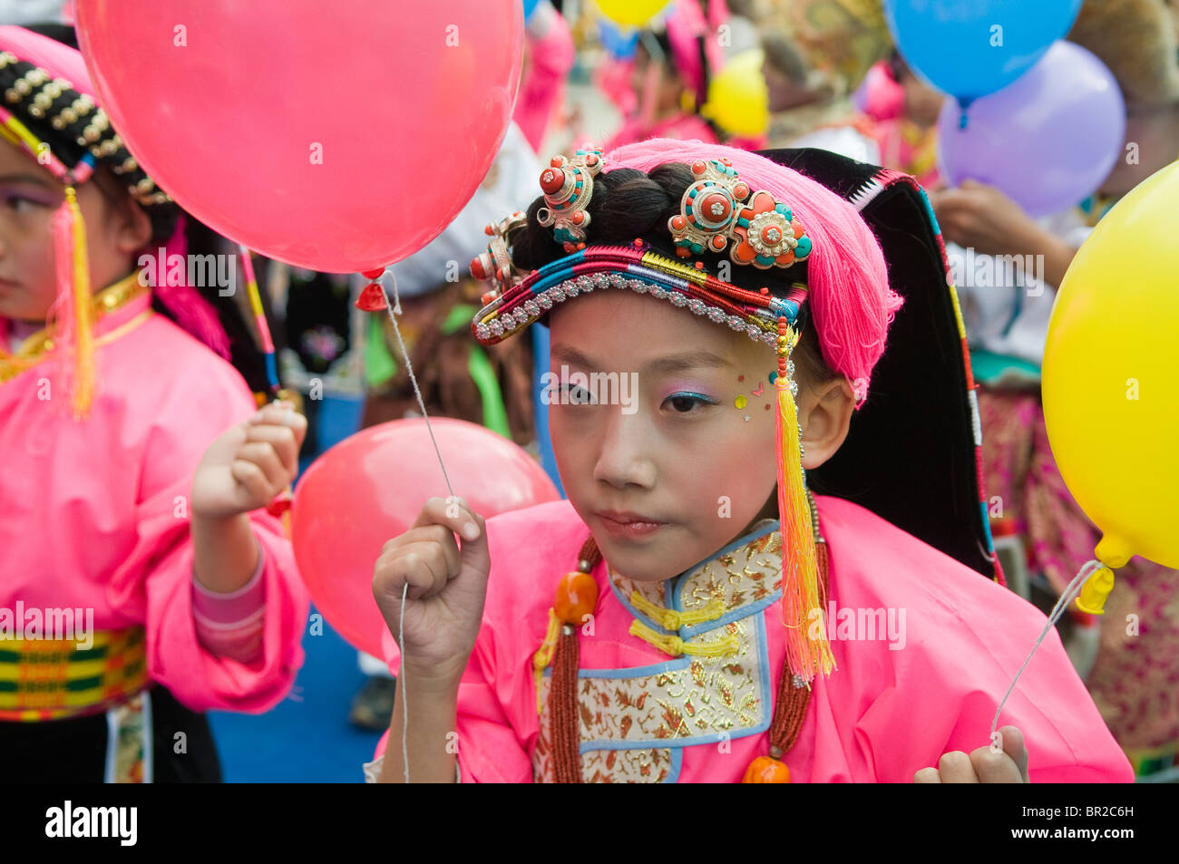 Young girl in ethnic Tibetan costume performs at dance and folk festival, Danba, Sichuan Province, China - Stock Image