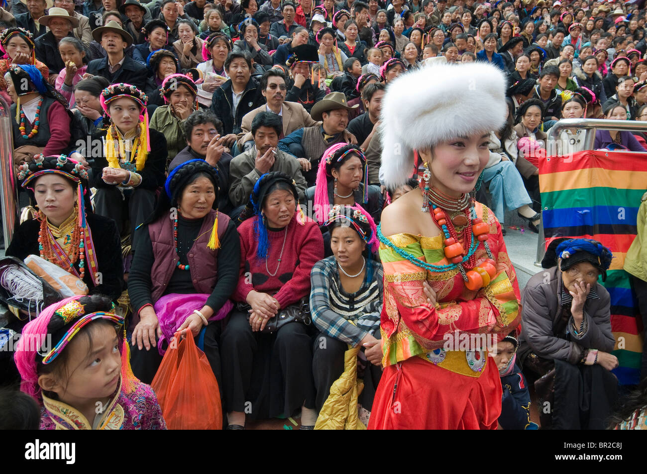 Singer wearing Ethnic Tibetan costume and jewelry waits to perform at folk festival, Danba, Sichuan Province, China - Stock Image