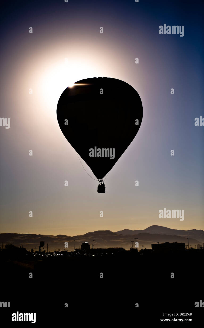 dawn silhouette of balloon against mountains and sunrise - Stock Image