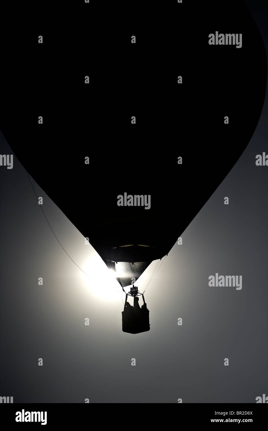 dawn silhouette of balloon with sun behind the basket - Stock Image