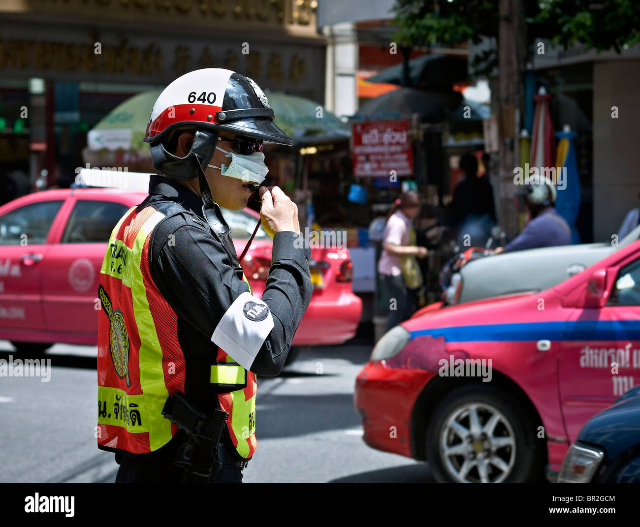 Thai police officer wearing an anti pollution mask in Bangkok's high pollution traffic flow. S. E. Asia - Stock Image