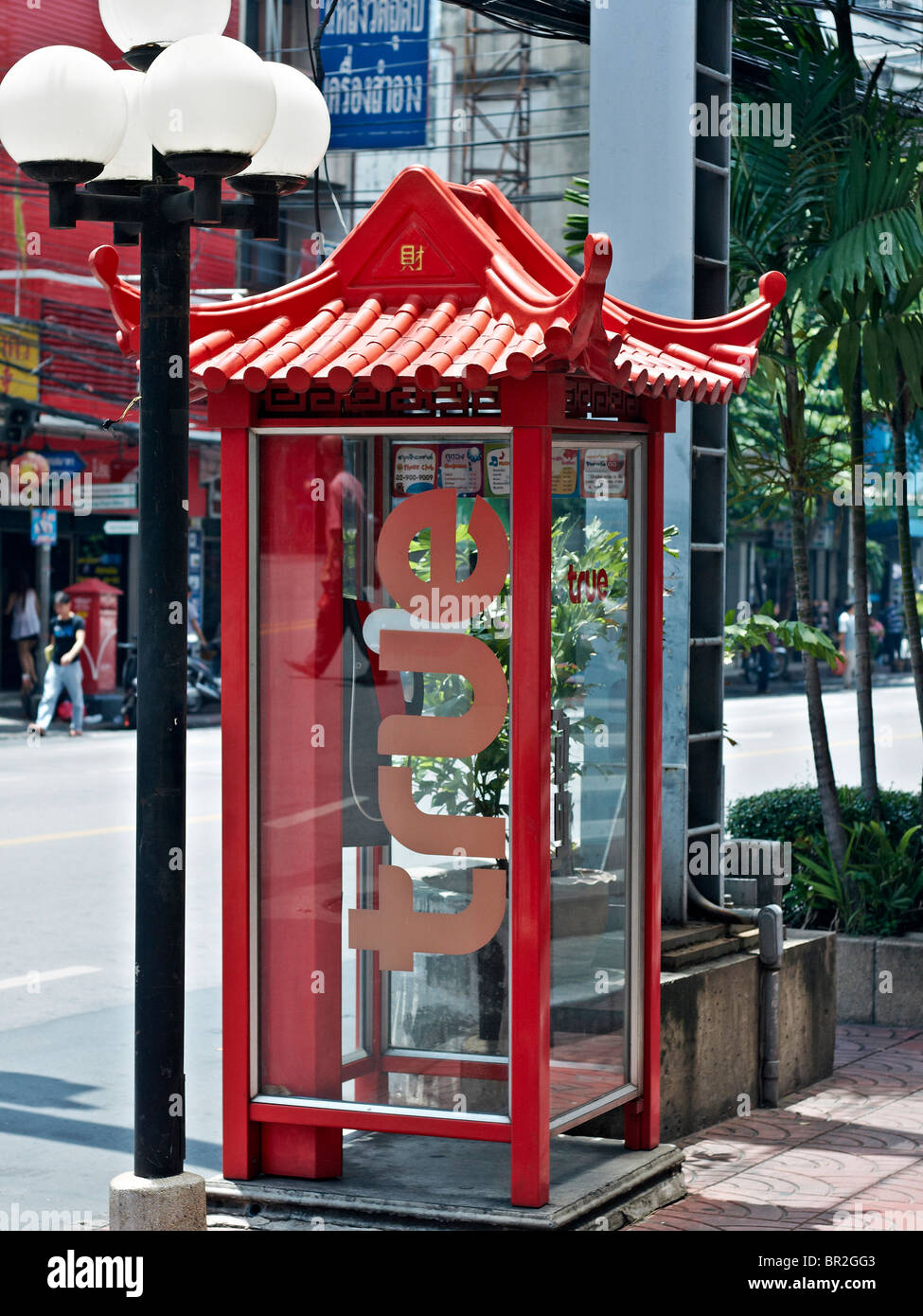 Chinese styled red telephone kiosk and accompanying decorative lantern in Bangkok's China Town district. Thailand - Stock Image