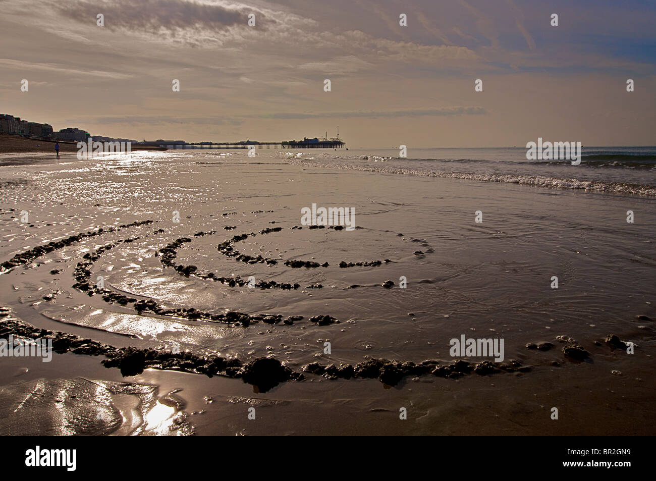 Brighton beach at low tide with the Palace Pier (now called Brighton Pier) beyond. East Sussex, England. Circles - Stock Image