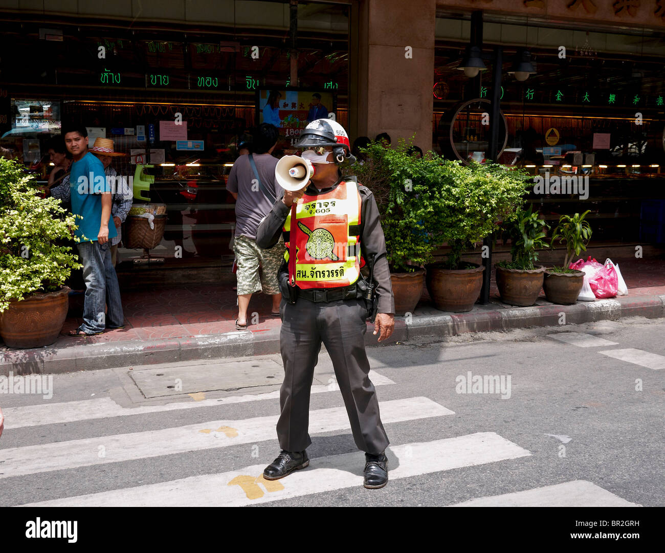 Thai police officer using a bull horn to control traffic in the noisy Bangkok city centre. Thailand S. E. Asia - Stock Image