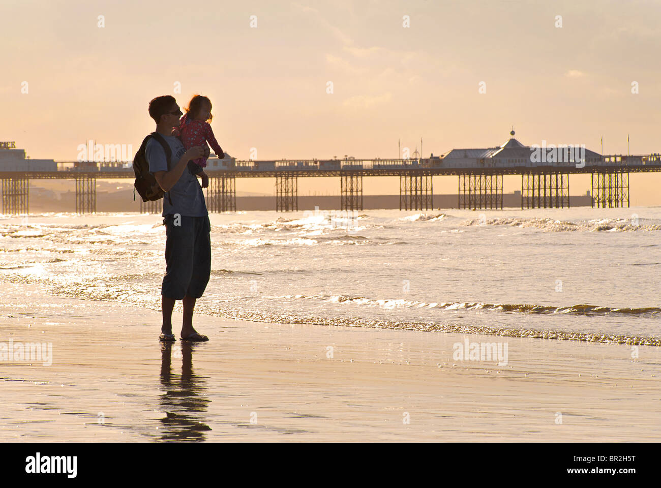 Father and young daughter on Brighton beach at low tide and sunrise. MODEL RELEASED. Brighton, East Sussex, England - Stock Image