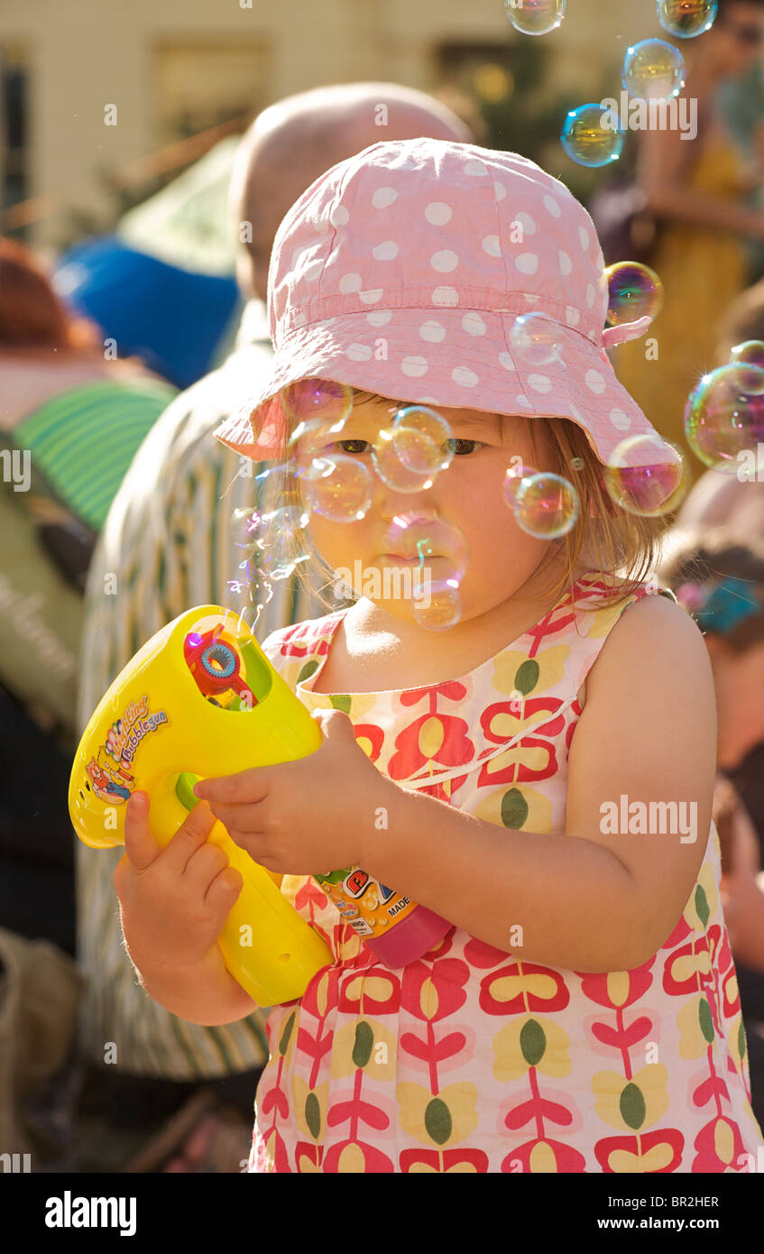 MODEL RELEASED. Young girl aged 2 blowing bubbles with a bubble gun. Brighton and Hove, East Sussex, England - Stock Image