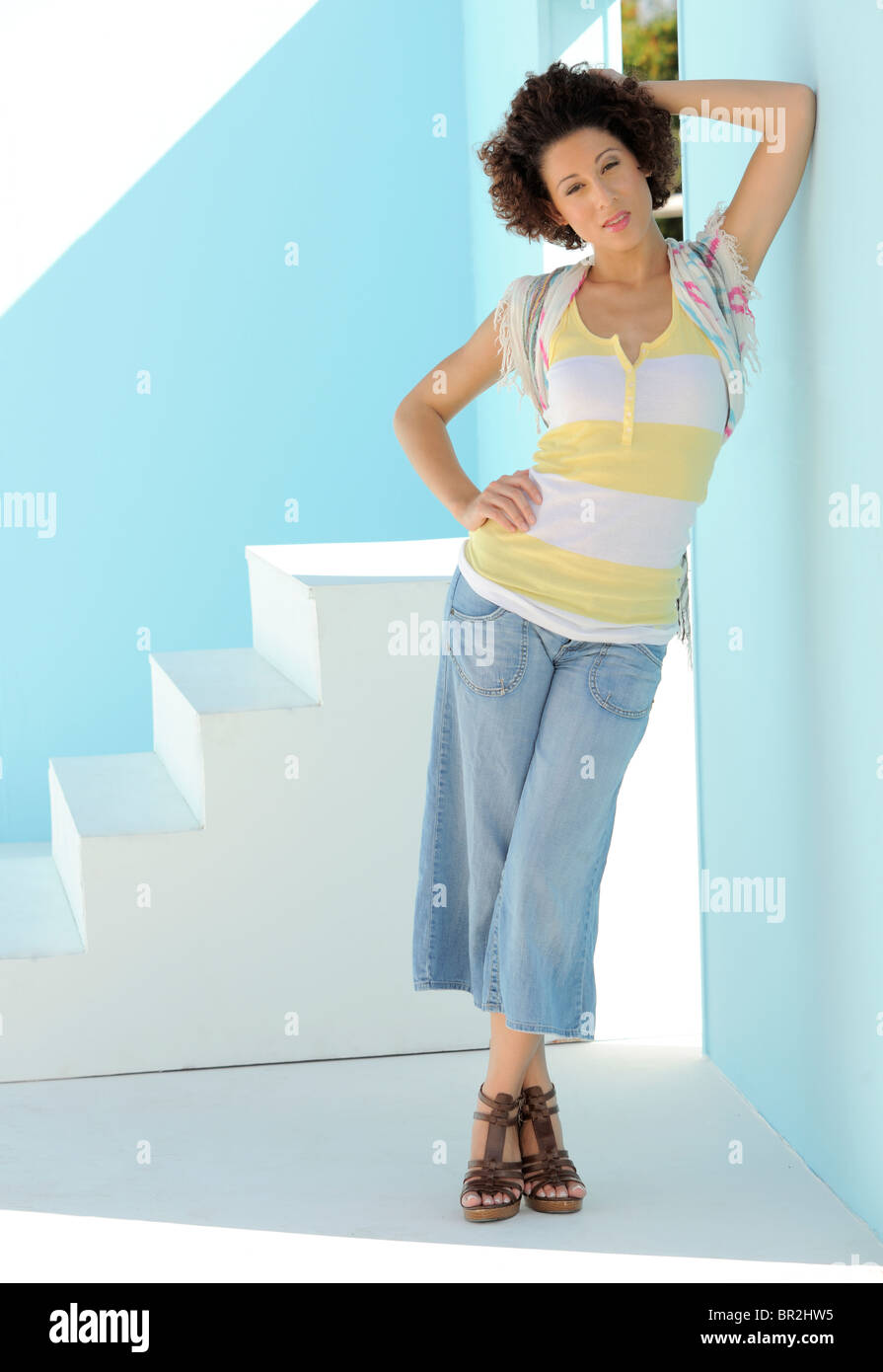 367805684f0a Beautiful Hispanic model leaning in the shade of a blue wall in ...
