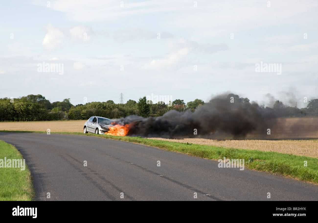 Car on roadside verge with it's engine on fire. - Stock Image