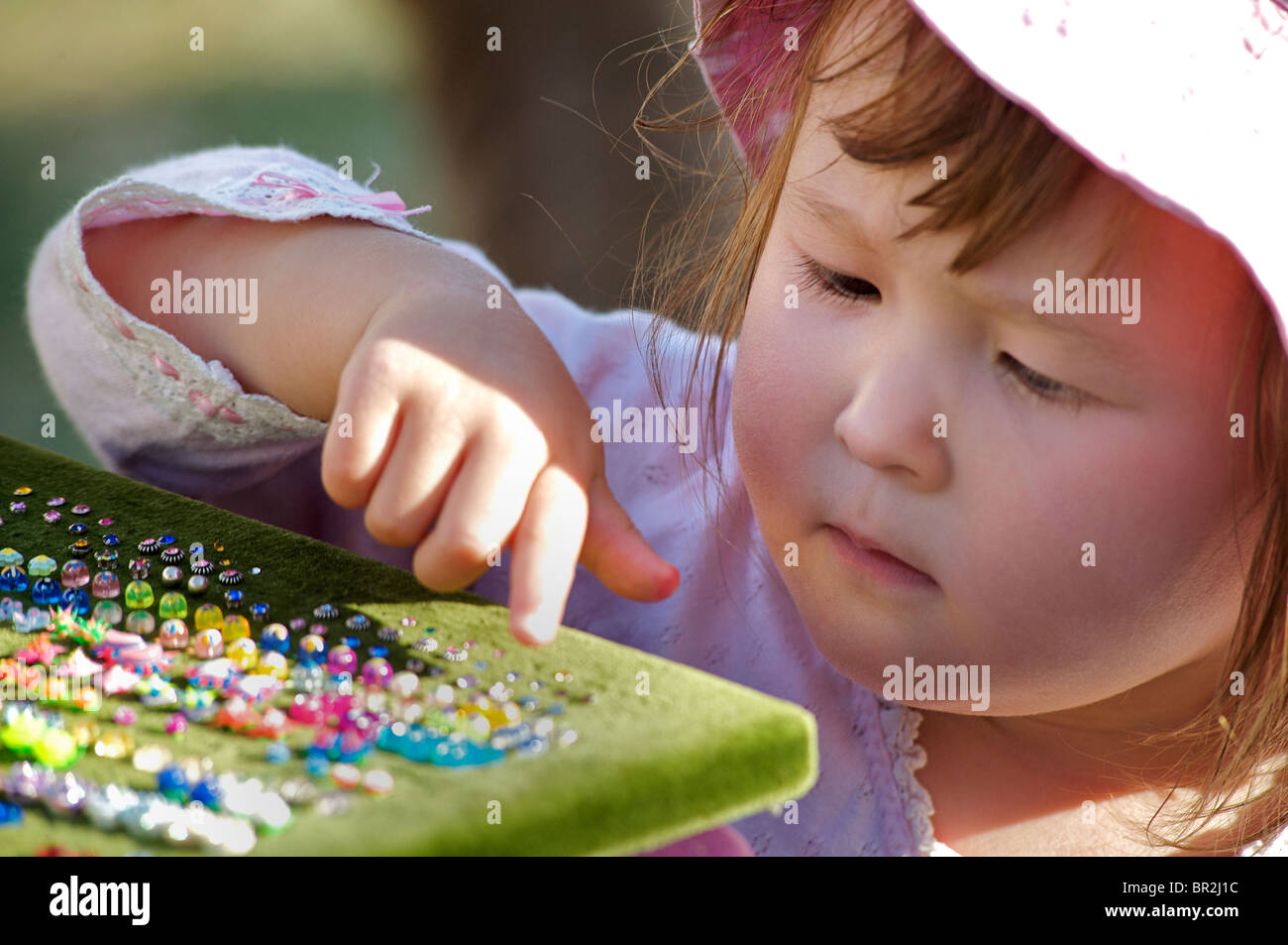 MODEL RELEASED. Young girl aged 2 admiring jewellery on a market stall - Stock Image