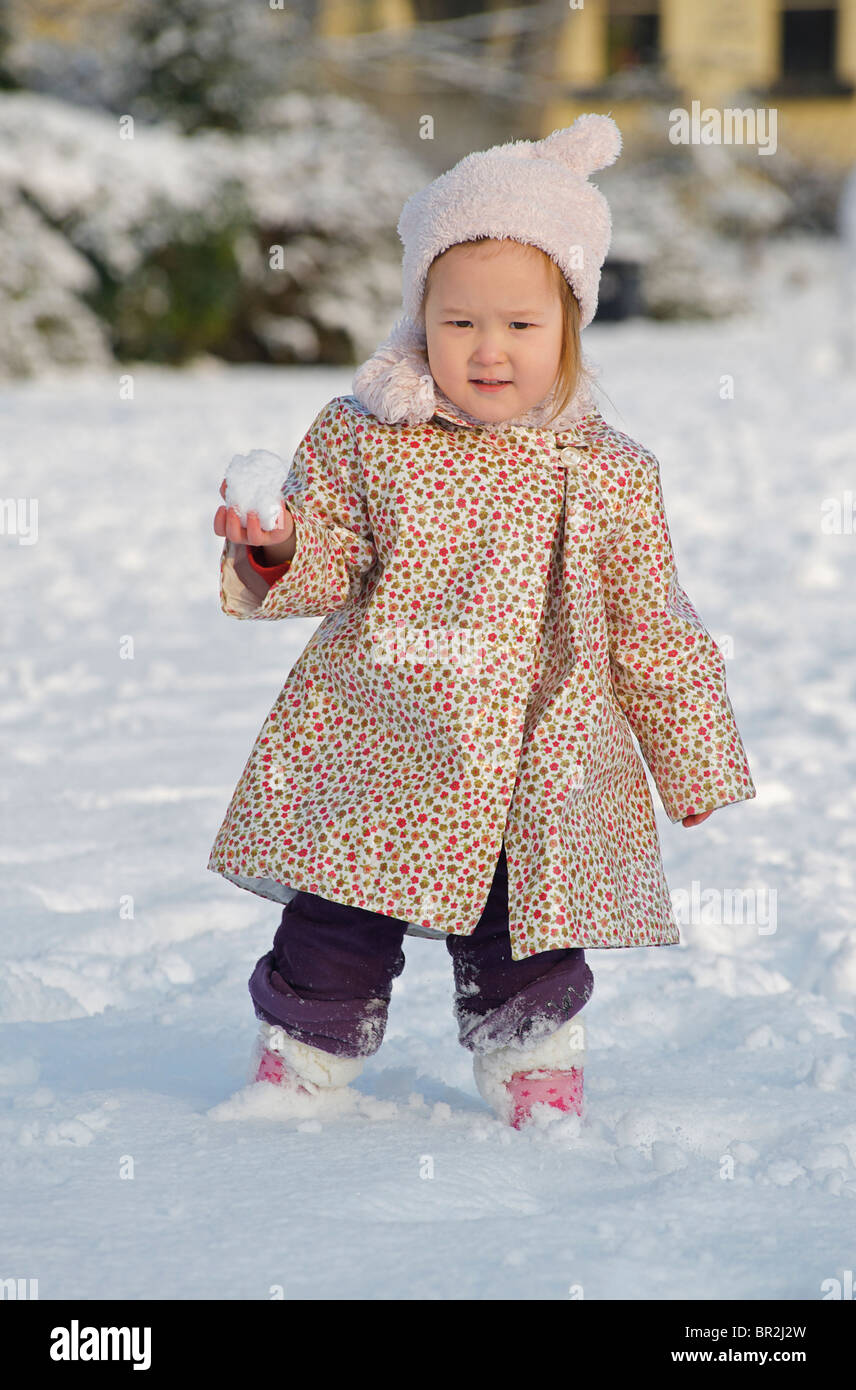 Toddler aged 2-3 with menacing intent. Snowball in hand. MODEL RELEASED - Stock Image