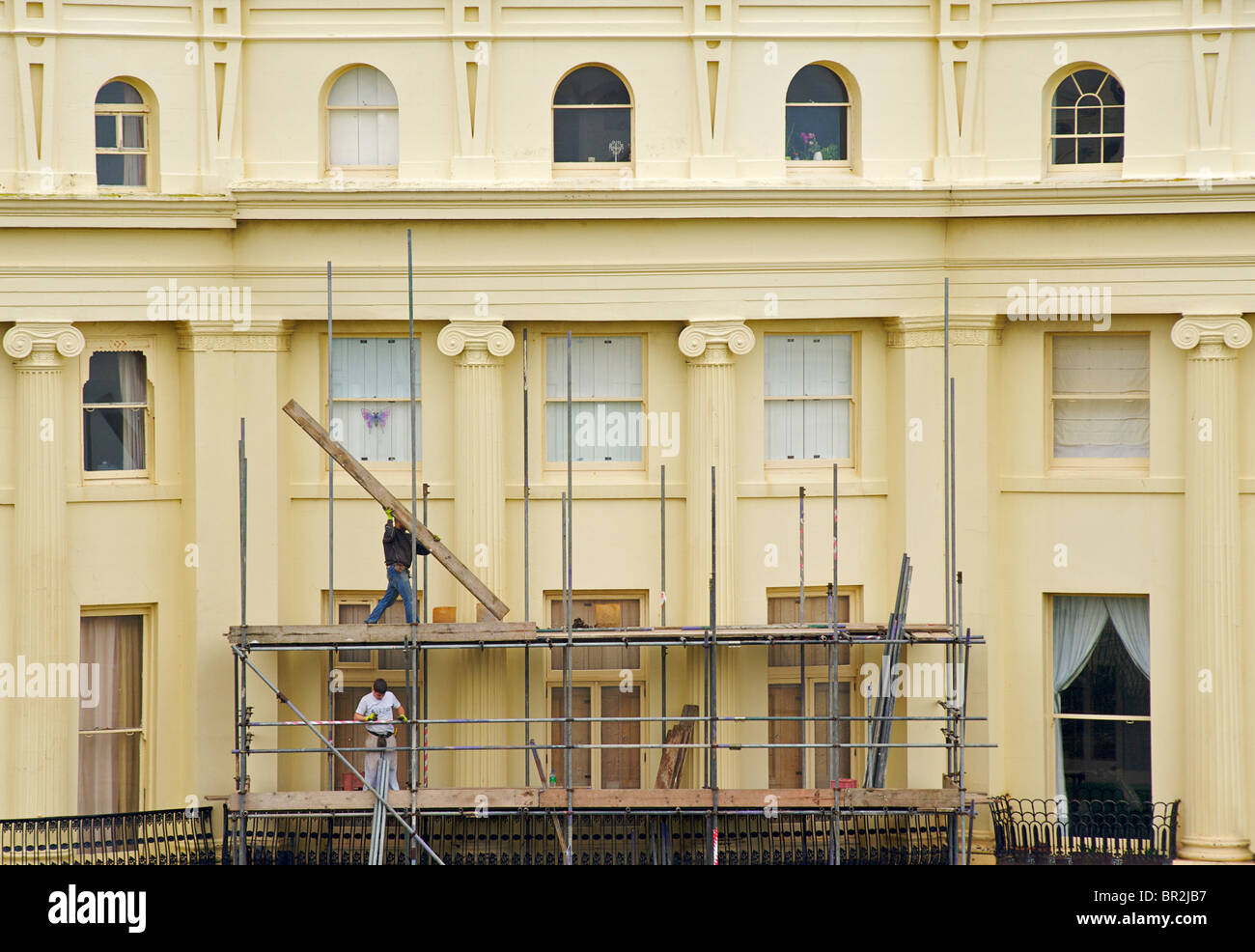 The Georgian buildings of Brunswick Square are repainted every 5 years. Scaffolders at work. Hove, East Sussex, - Stock Image