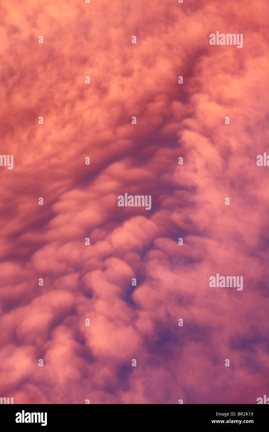 Brightly colored clouds at sunset - Stock Image