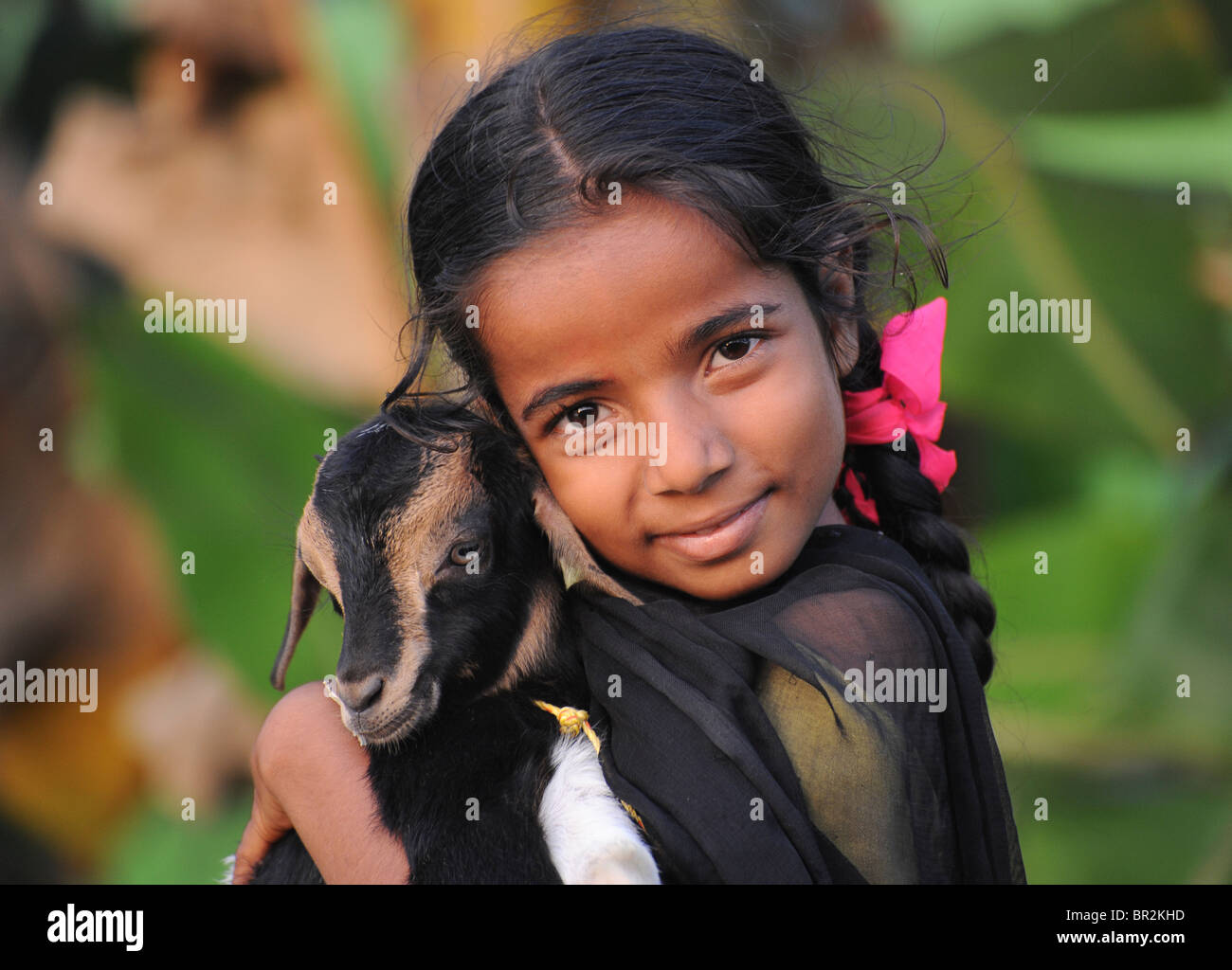 Portrait of an Indian girl with a goat, Kerala, India - Stock Image