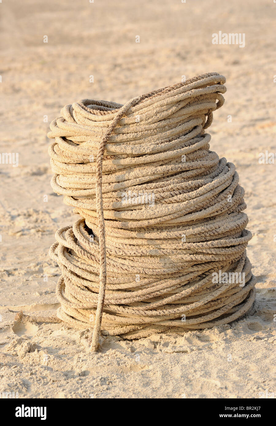 Coil of sandy rope on a beach - Stock Image