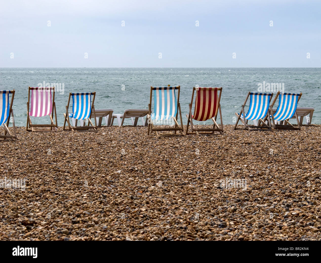 Empty deckchairs on a deserted pebble beach-1 - Stock Image