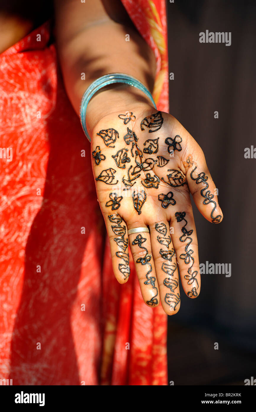 Indian woman having hands decorated with henna paint. Goa, India - Stock Image