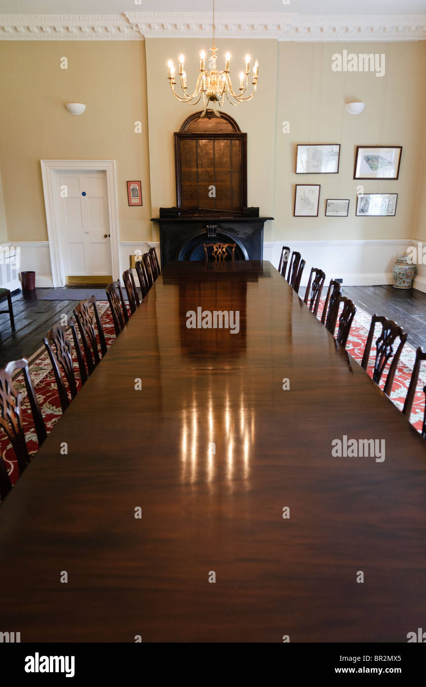 Long, old fashioned polished wooden dining table with chairs in a dining room Stock Photo