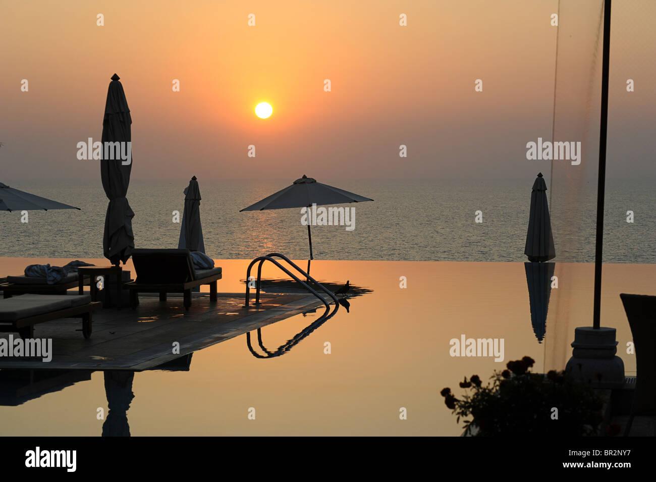 Hotel infinity pool at sunset, Kovalam, Kerala, India Stock Photo