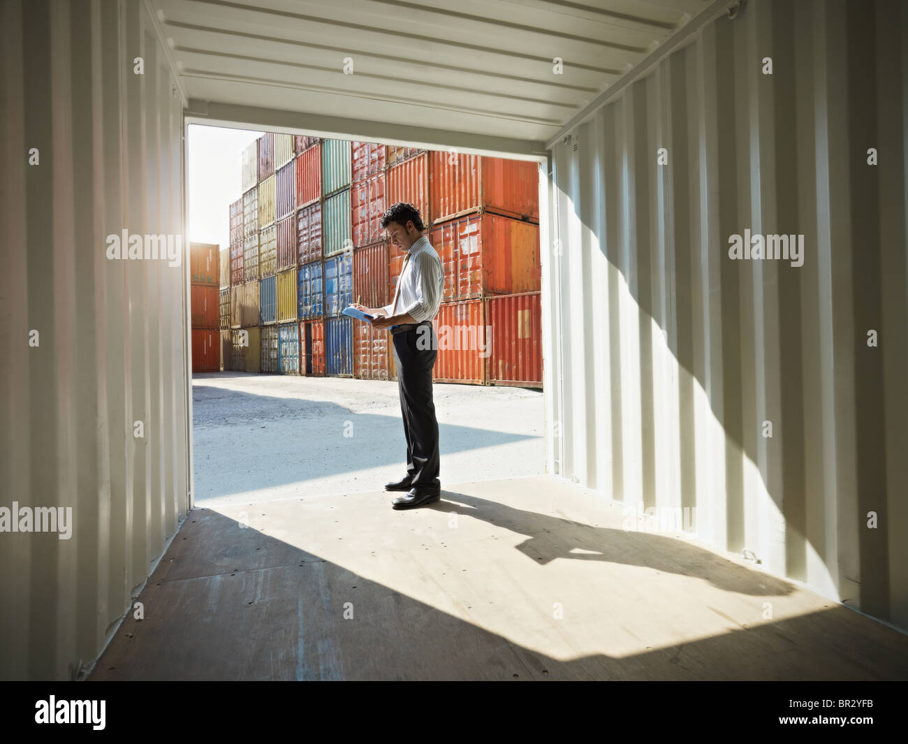 businessman with clipboard in shipping container - Stock Image