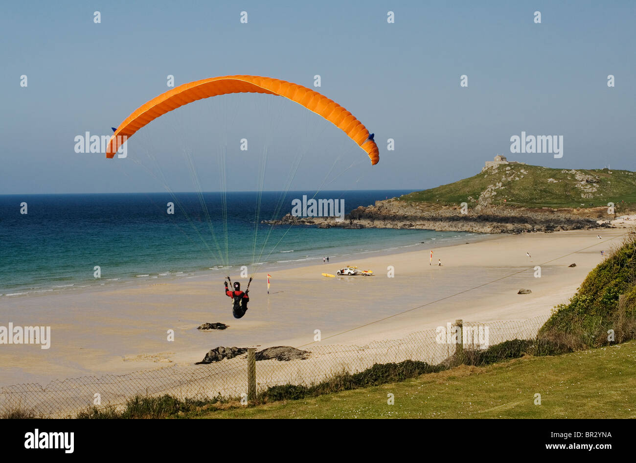 Colorful Hang Glider Flying Over Porthmeor Beach, Saint Ives, Cornwall. Stock Photo