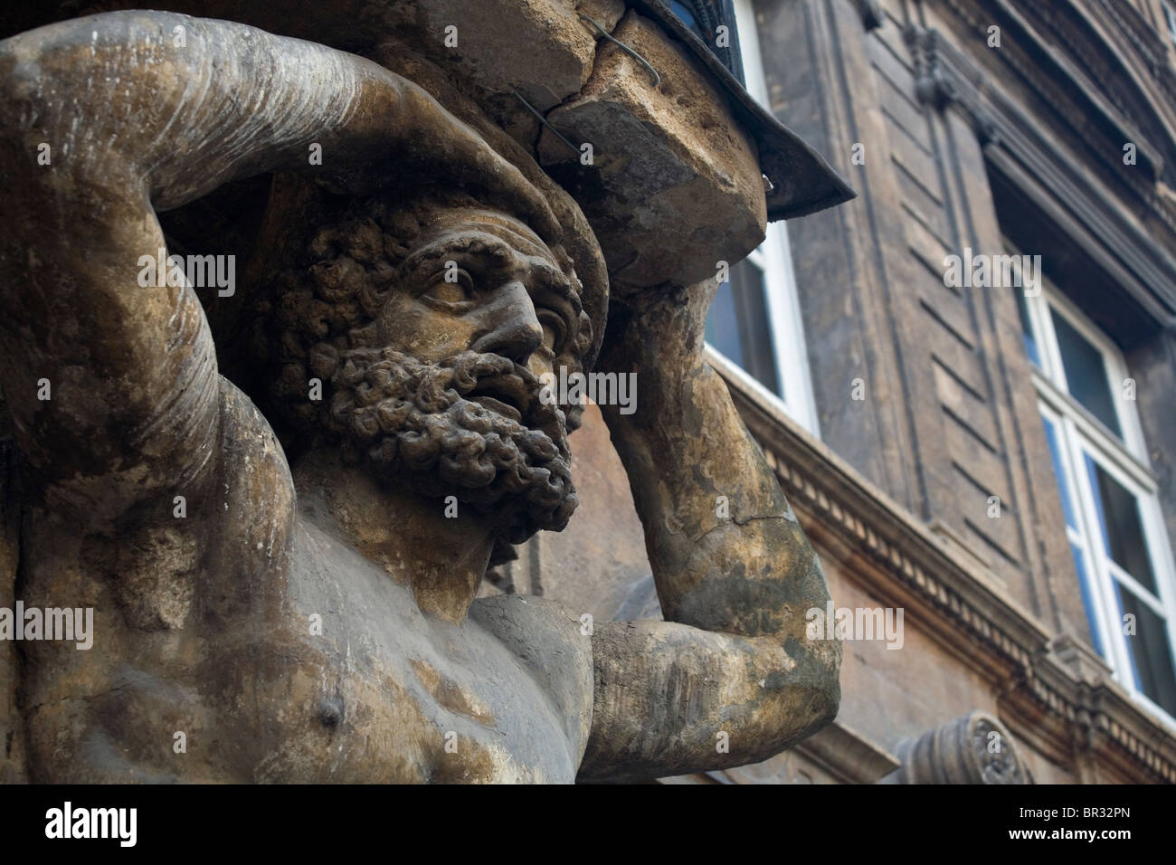 Enormous statue of a man holds a balcony with his head. - Stock Image