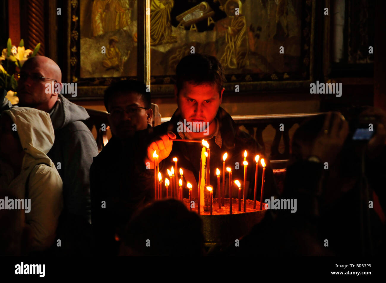 Christian pilgrim lights a candle in front of the birth grotto in the Chapel of the Nativity of Christ in Bethlehem, - Stock Image