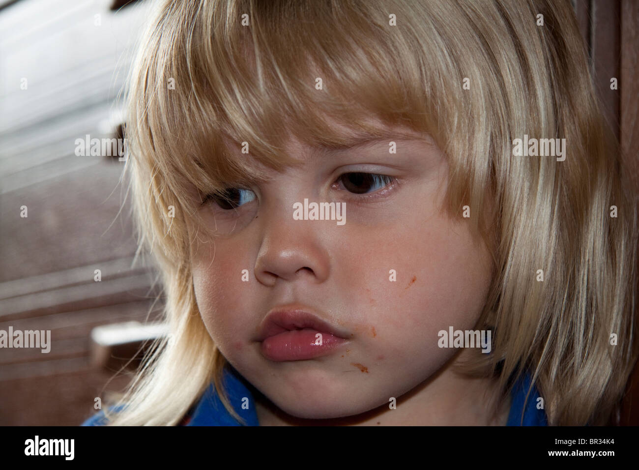 Boy with long blonde hair and a dirty face sulking - Stock Image