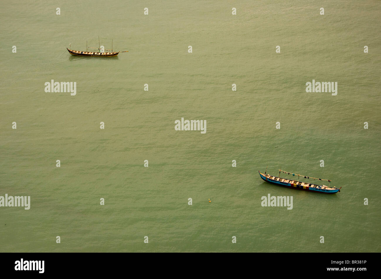 Two small traditional Ghanaian fishing boats at anchor in calm midday waters off the shore of  Cape Coast. Stock Photo